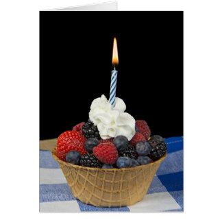 Cartão bagas e vela do aniversário na bacia do waffle