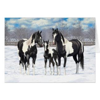 Cartão Cavalos pretos da pintura na neve