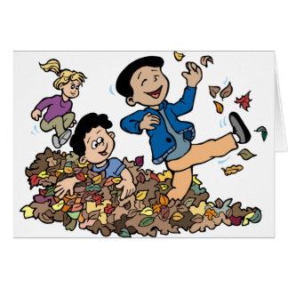 Cartão Crianças que jogam nas folhas