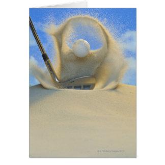 Cartão cunha de areia que bate uma bola de golfe fora de