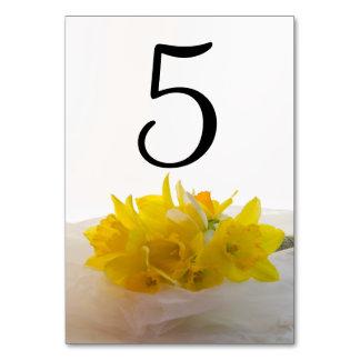 Cartão Daffodils amarelos nos números brancos da mesa do