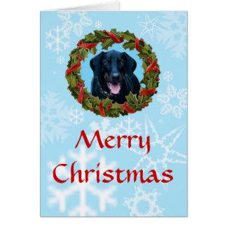 Cartão de Natal preto do Doberman com grinalda e