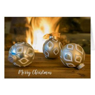 Cartão enfeites de natal do ouro pela lareira