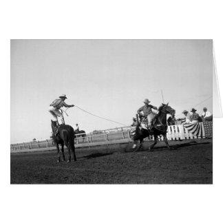 Cartão Equipe a posição em um cavalo que roping um cavalo