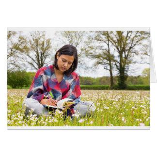 Cartão Escrita da mulher no prado com flores do primavera