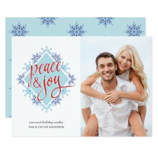 Cartão Escrita da paz & da alegria sobre flocos de neve