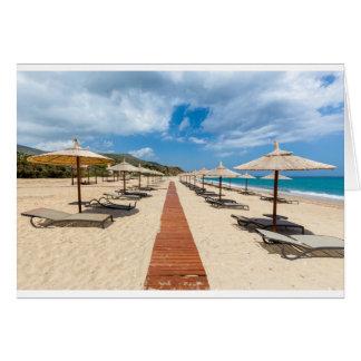 Cartão Guarda-chuvas de praia e loungers no mar grego