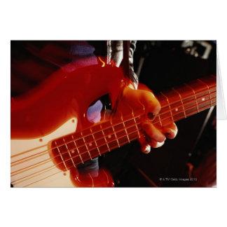 Cartão Homem novo que joga a guitarra baixa, fim-acima da