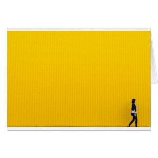 Cartão Menina que anda contra a parede amarela enorme