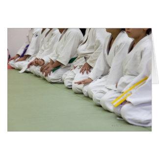 Cartão O jogador do judo da criança senta-se para baixo a