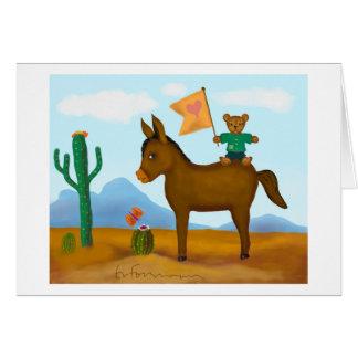 Cartão O urso de ursinho monta um asno no deserto