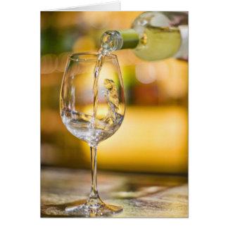 Cartão O vinho branco é derramado da garrafa no