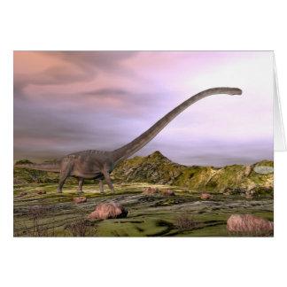 Cartão Omeisaurus que anda no deserto pelo por do sol