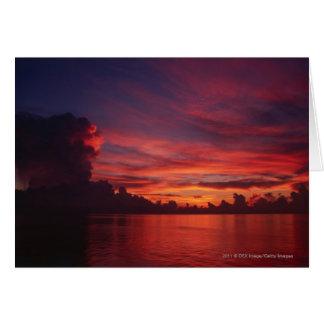 Cartão Por do sol no mar com nuvens escuras