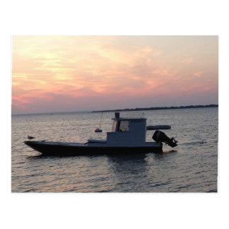 Cartão Postal Barco dos moluscos na baía no por do sol