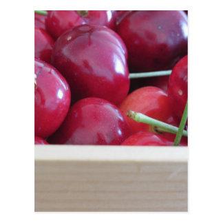Cartão Postal Beira de cerejas frescas no fundo de madeira