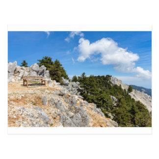 Cartão Postal Bench na montanha rochosa com árvores e o céu azul