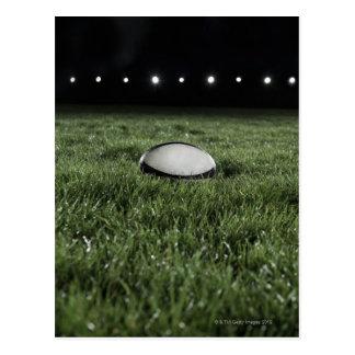 Cartão Postal Bola de rugby que senta-se no passo da grama da