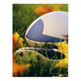 Cartão Postal Bola e calçados de rugby no gramado no outono