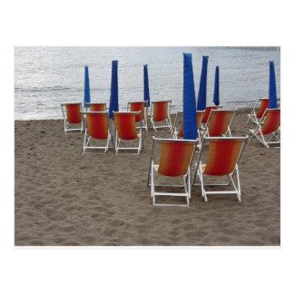 Cartão Postal Cadeiras de madeira coloridas na praia da areia