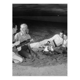 Cartão Postal Dois casais na praia que senta-se em torno da