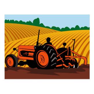 Cartão Postal fazendeiro que conduz o trator de fazenda que ara