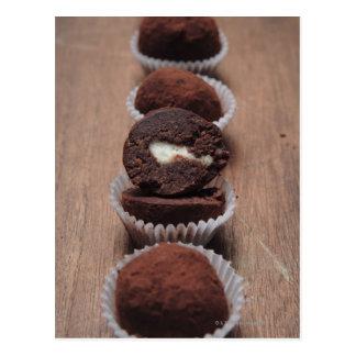 Cartão Postal Fileira de trufas de chocolate na madeira