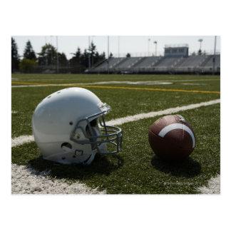 Cartão Postal Futebol e capacete de futebol no campo de futebol