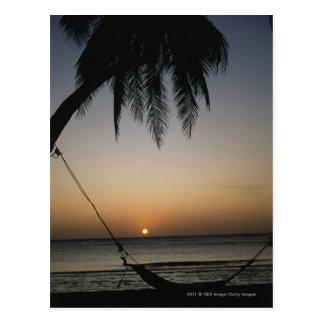 Cartão Postal Hammock vazio de Silhuetted no por do sol