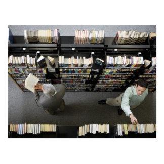 Cartão Postal Homens na biblioteca que procura livros