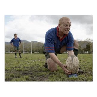 Cartão Postal Jogador do rugby que posiciona a bola sobre o