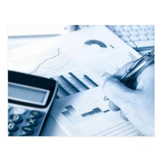 Cartão Postal mão e caneta escrevendos entre figuras financeiras