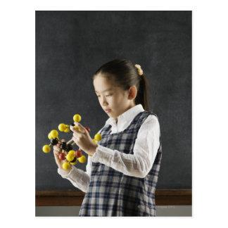 Cartão Postal Menina asiática que olha o modelo da molécula