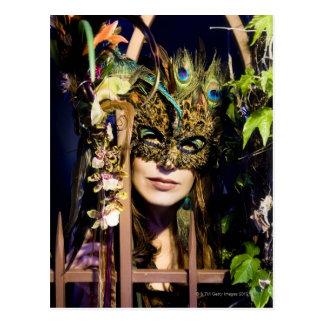 Cartão Postal Mulher que veste uma máscara que olham para fora