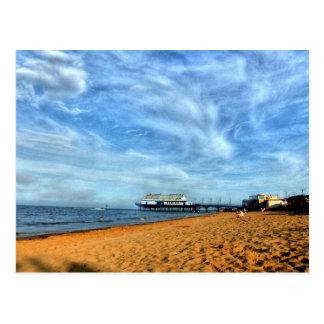 Cartão Postal Praia brilhante sereno com cais & as nuvens