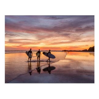 Cartão Postal Surfistas no por do sol que andam na praia, Costa
