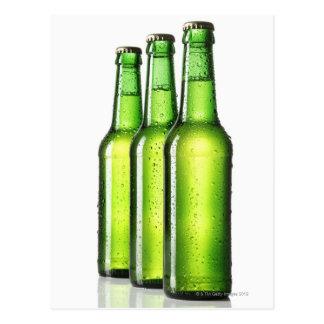 Cartão Postal Três garrafas verdes da cerveja no fundo branco,
