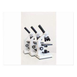 Cartão Postal Três microscópios em seguido isolados no fundo