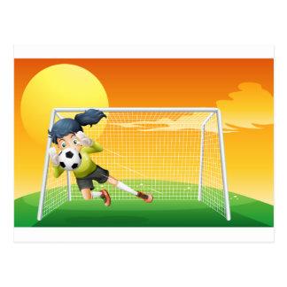 Cartão Postal Um jogador de futebol fêmea que trava a bola