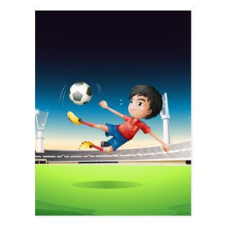 Cartão Postal Um menino em um uniforme vermelho no campo de