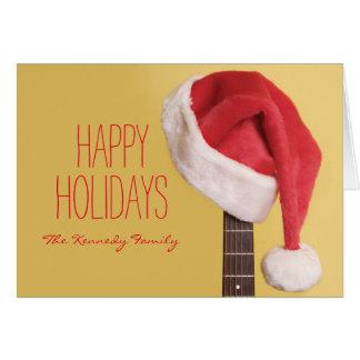 Cartão Um chapéu do papai noel pendura em uma guitarra
