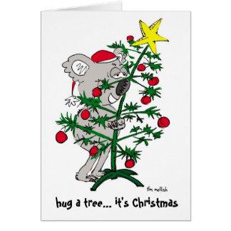 Cartão Urso de Koala que abraça uma árvore de Natal