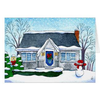 Casa bonito do Natal com cartão do boneco de neve