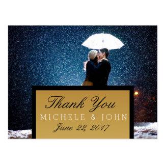 Casal com guarda-chuva que beija na neve/obrigado cartão postal