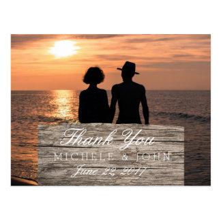 Casal romântico que guardara as mãos no por do cartão postal