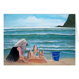 Castelo da areia da construção da menina nos cartõ cartão de nota