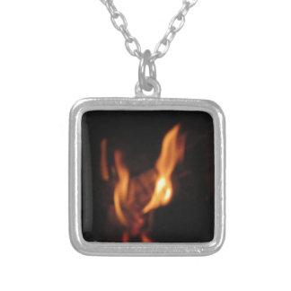 Chamas borradas em uma lareira ardente no preto colar banhado a prata