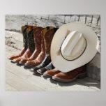Chapéu de vaqueiro na fileira de botas de vaqueiro poster