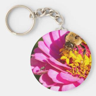 Chaveiro abelha e inseto que estão em uma flor roxa