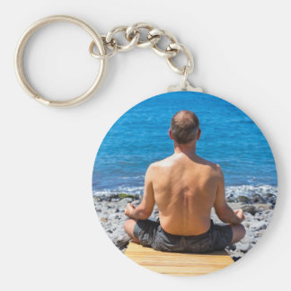 Chaveiro Homem que meditating na praia e no mar